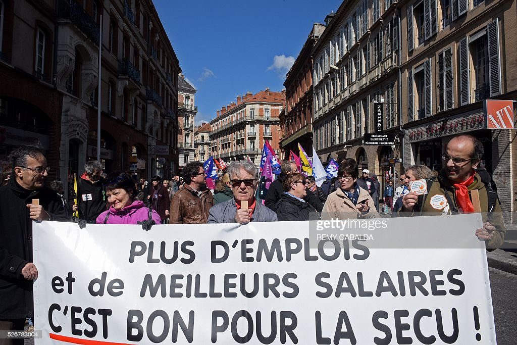 Participants walk with a banner reading 'More employment and better salaries - that's good for the social security' as they protest against the government's proposed labour law reforms during the traditional May Day demonstration in Toulouse, southern France, on May 1, 2016. / AFP / REMY