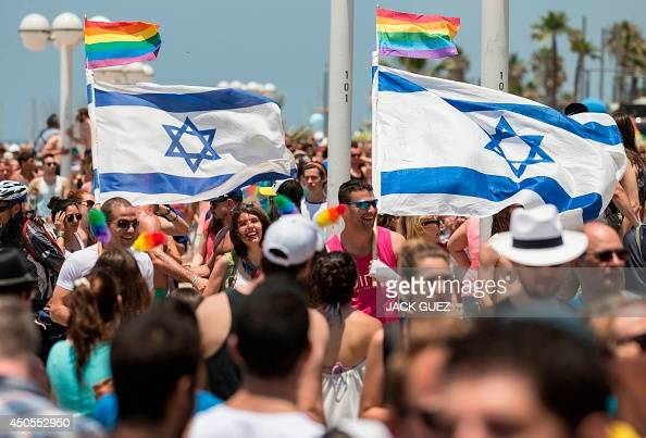 Participants wave Israeli's flags during the annual gay pride parade in the Israeli coastal city of Tel Aviv on June 13 2014 AFP PHOTO/JACK GUEZ