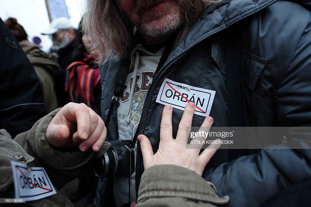 Participants wear anti Hungarian Prime Minister Viktor Orban stickers during an anti-government demonstration in front of the headquarters of the FIDESZ paty in Budapest on March 30, 2013. The fourth constitutional modification of the basic law will be come into force on April 1.