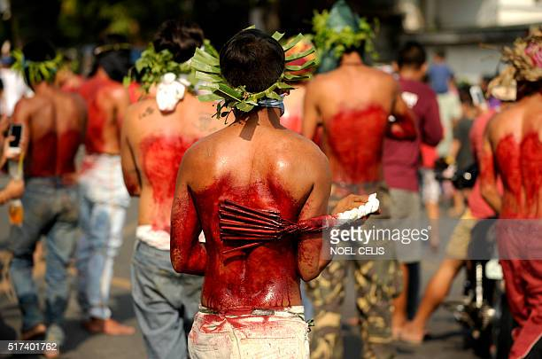 TOPSHOT Participants whip their bloodied backs with bamboo as part of their penitence during the reenactment of the crucifixion of Jesus Christ for...