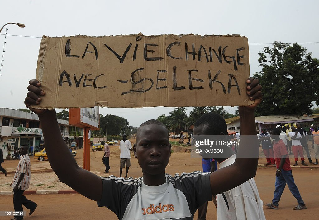 A partisans of new Central African Republic leader Michel Djotodia holds a banners during a support march in the streets of Bangui on March 30, 2013. The Central African Republic's new strongman Michel Djotodia vowed Saturday not to contest 2016 polls and hand over power at the end of the three-year transition he declared after his coup a week ago. (placrd reads in french, ' Seleka, that life, game over').