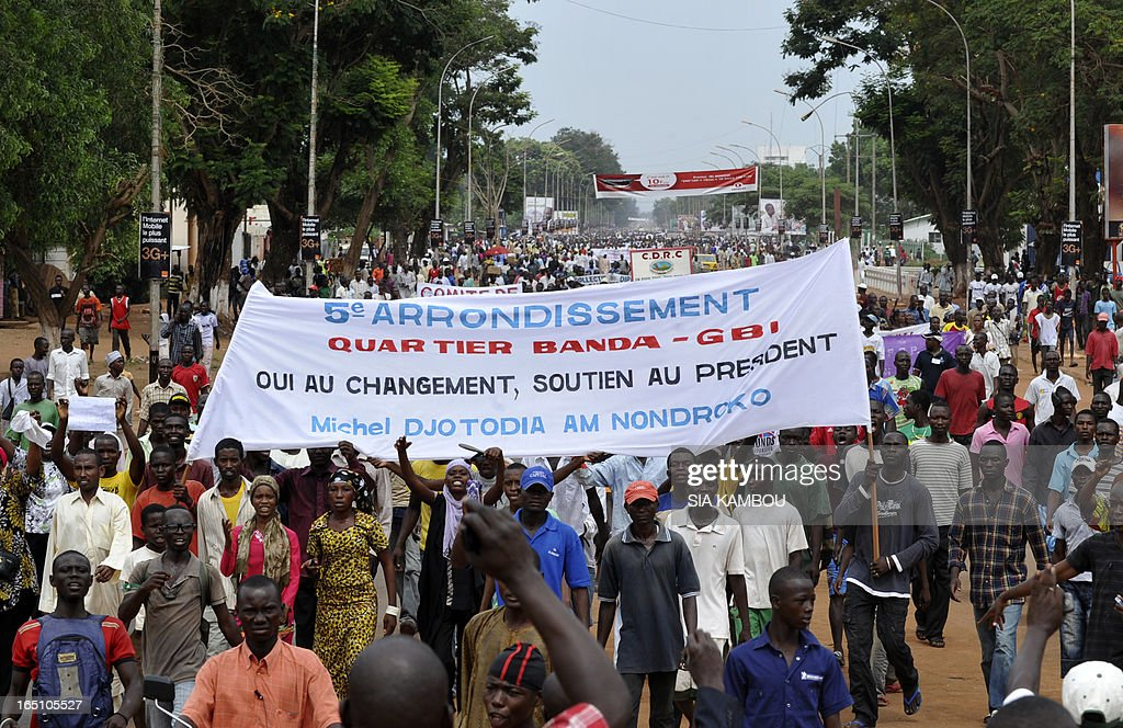Partisans of new Central African Republic leader Michel Djotodia hold flags and banners during a support march in the streets of Bangui on March 30, 2013. The Central African Republic's new strongman Michel Djotodia vowed Saturday not to contest 2016 polls and hand over power at the end of the three-year transition he declared after his coup a week ago. (banner reads; 5th districj, Banda-GB quarter, Yes to change, Support the President Michel Djotodia Am Nondroko ').