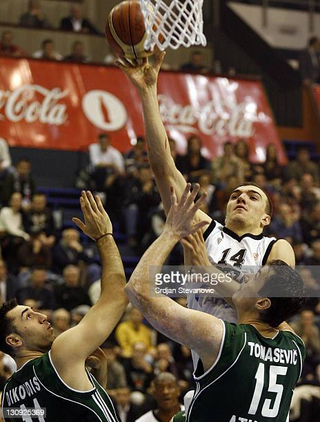 Partizan Belgrade player Nikola Pekovic above try to score over Dejan Tomasevic right and Dimitris Dikoudus left from Panathinaikos Athens during...