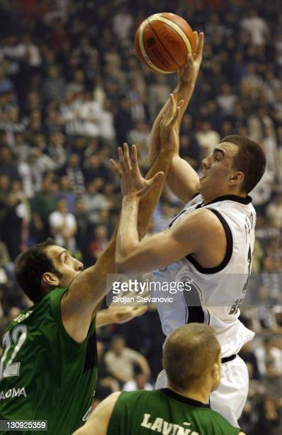 Partizan player Nikola Pekovic above tries to score over Roberto Duenas left during a group B Euroleague basketball match between Partizan and...