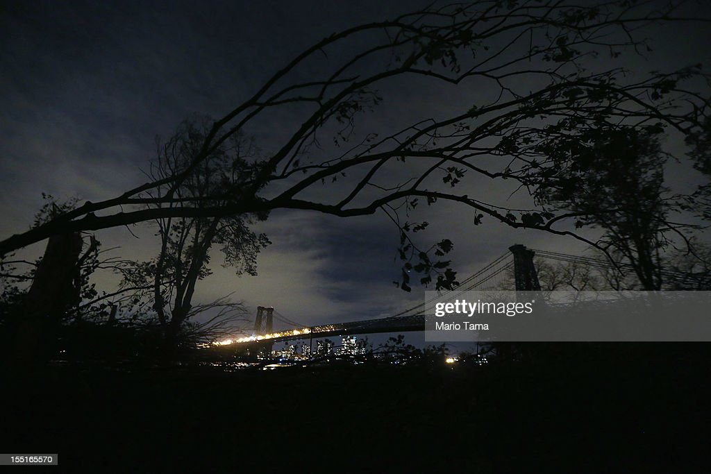 Parts of a fallen tree dangle in front of the Williamsburg Bridge, lit on the Brooklyn side (L) but darkened on the Manhattan side on November 1, 2012 in New York, United States. Most residents of Lower Manhattan remain without power following Superstorm Sandy. Lower Manhattan residents should have power restored Saturday while most others in the city should have power by November 10 or 11.