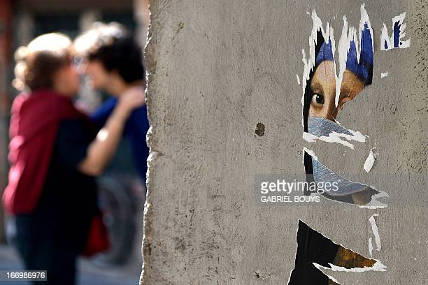 Parts of a mural showing the Girl with a Pearl Earring by Johannes Wermeer with a mouth cover are displayed on a wall in Rome on April 19 2013 The...