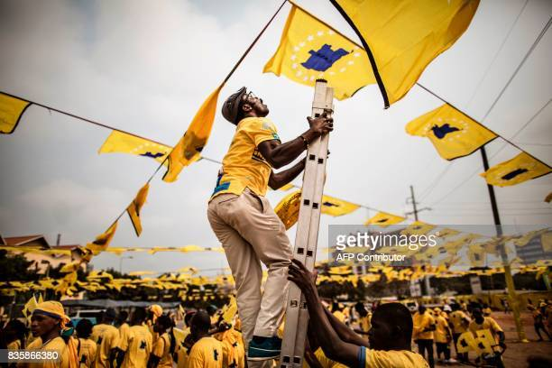 TOPSHOT A party activist puts the final touches to decorations before the leader of the Angolan opposition party CASACE Abel Chivukuvuku addresses an...