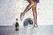 Party detail with woman legs in red high heels and disco ball