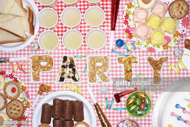 Party food on table in dishes spelling 'PARTY', overhead view