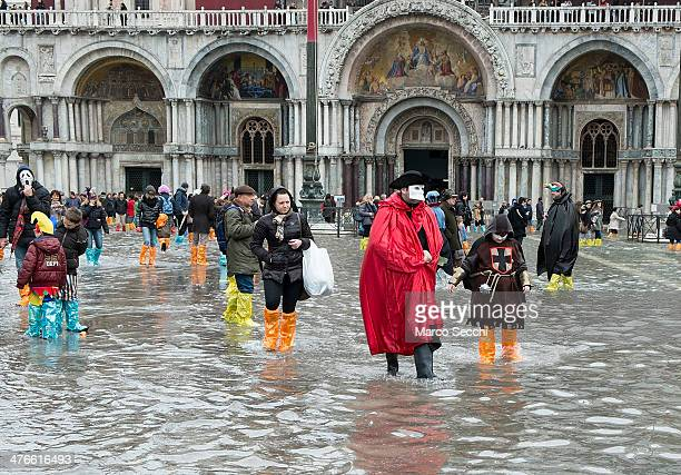 Party goers wear boots with their costumes and masks as they walk in flooded Saint Mark's Square on the last day of Carnival on March 4 2014 in...
