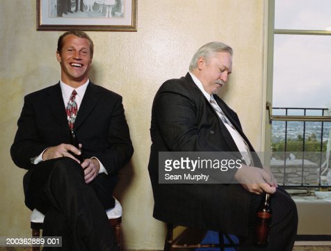Party guests sitting against wall, one man sleeping : Stock Photo