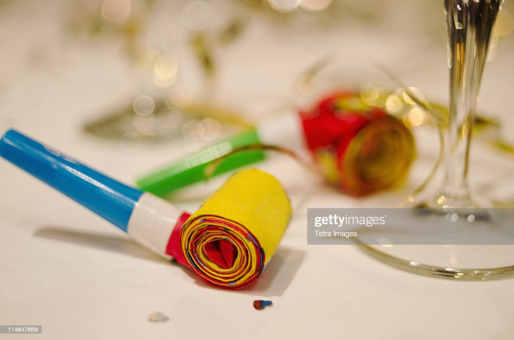 Party horn blower and champagne flute on table, close-up