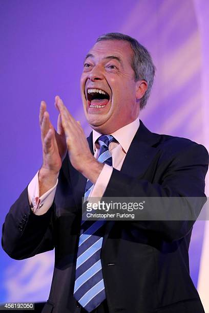 UKIP party leader Nigel Farage cheers and applauds as Conservative MP Mark Reckless arrives on stage to announce he was defecting from the tories on...