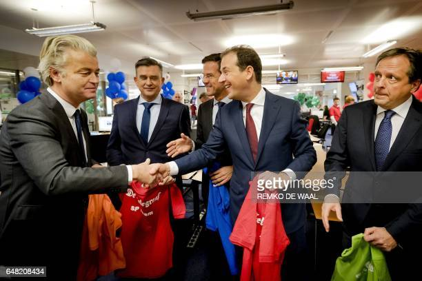 Party leaders Geert Wilders and Lodewijk Asscher shake hands as they visit the newsroom of Dutch daily newspaper De Telegraaf on March 5 2017 in...