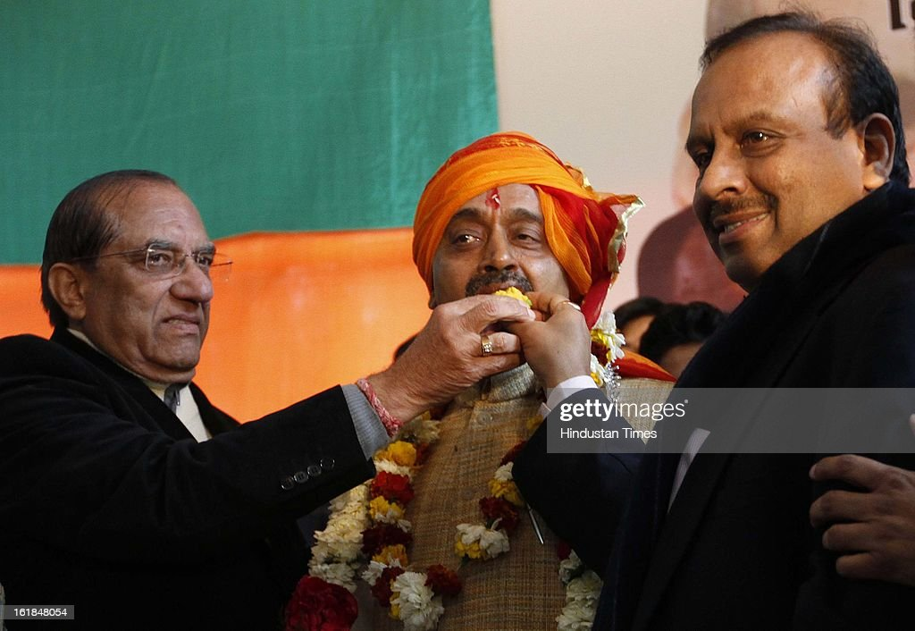 Party leaders greet and offering sweets to their Newly appointed BJP Delhi Pradesh President Vijay Goel as former president of BJP Delhi Pradesh Vijender Gupta (R) looks on at a function at BJP office on February 17, 2013 in New Delhi, India.