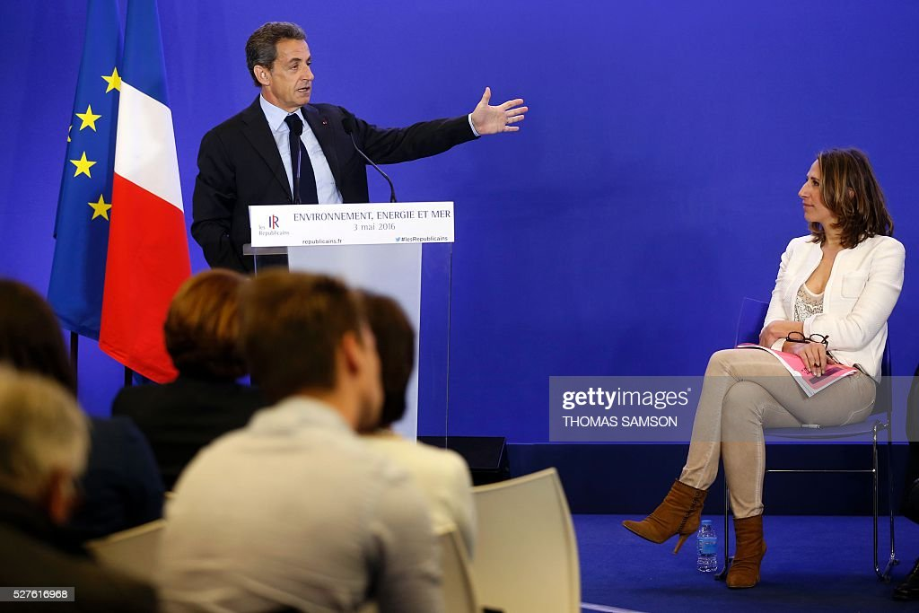 LR party member and general delegate in charge of Environment Maud Fontenoy (R) listens to the former French president and president of France's right-wing Les Republicains (LR) party Nicolas Sarkozy as he speaks after a meeting on environment, sea and energy, at the party's headquarters in Paris on May 3, 2016. SAMSON