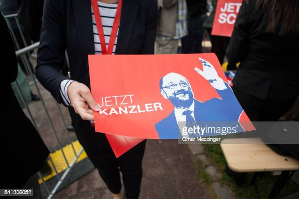 A party member is handing out poster with the image of Martin Schulz chancellor candidate of the German Social Democrats prior to his arrival on a...
