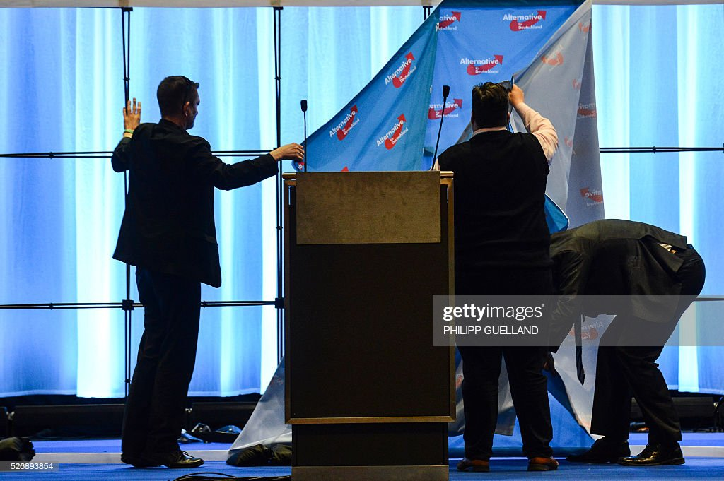 Party members dismantle a portable backdrop after the german right wing party Alternative for Germany (AfD) party congress at the Stuttgart Congress Centre ICS on May 1, 2016 in Stuttgart, southern Germany. Germany's right-wing populist AfD adopted an anti-Islam policy in a manifesto that also demands curbs to immigration, as a poll showed it is now the country's third strongest party. / AFP / Philipp GUELLAND