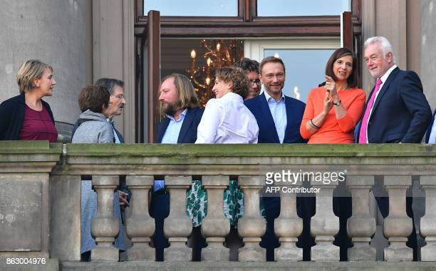 Party members of Germany's ecologist Greens and the liberal free democratic FDP party stand on a balcony of the venue where they are holding...