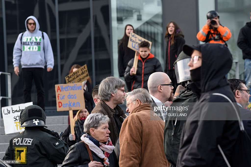 Party members stand in front of protesters as they arrive for a party congress of the German right wing party AfD (Alternative fuer Deutschland) at the Stuttgart Congress Centre ICS on April 30, 2016 in Stuttgart, southern Germany. Protesters tried to block the access to the party conference of the 'Alternative Fuer Deutschland' (Alternative for Germany) with around 400 being taken into custody. / AFP / Philipp GUELLAND