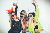 Three female friends posing in front of white wall. New year party