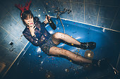 New Year's Party. Girl sitting in the bathtub, drinking and having fun