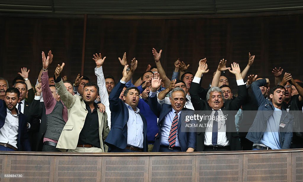AK Party supporters gesture as Turkish Prime Minister and the leader of Turkey's ruling party, the Justice and Development Party (AK Party) Binali Yildrim speaks during AK Party's group meeting at the Grand National Assembly of Turkey (TBMM) in Turkey on May 24, 2016. / AFP / ADEM