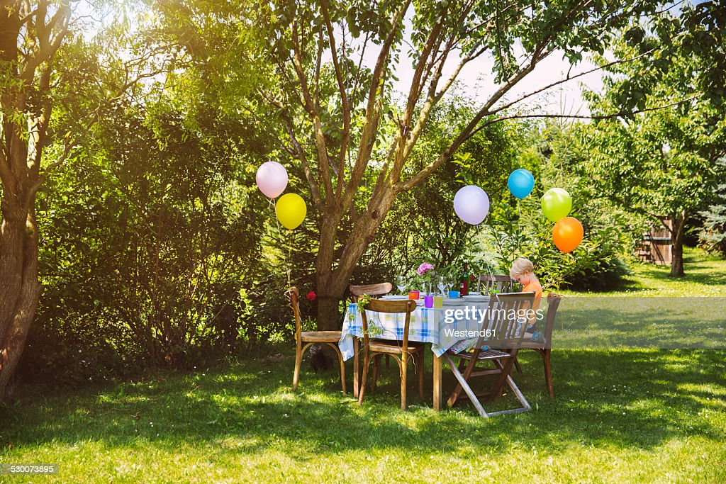Party table in garden with little boy