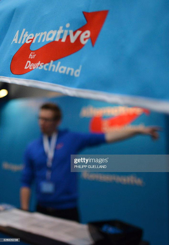 A party volunteer gestures at an information booth during a party congress of the German right wing party AfD (Alternative fuer Deutschland) at the Stuttgart Congress Centre ICS on April 30, 2016 in Stuttgart, southern Germany. The Alternative for Germany (AfD) party is meeting in the western city of Stuttgart, where it is expected to adopt an anti-Islamic manifesto, emboldened by the rise of European anti-migrant groups like Austria's Freedom Party. / AFP / Philipp GUELLAND