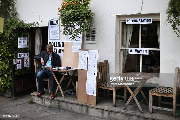 A party worker sits outside The Anglesea Pub which is open as a polling station on May 22 2014 in London England Millions of voters are going to the...