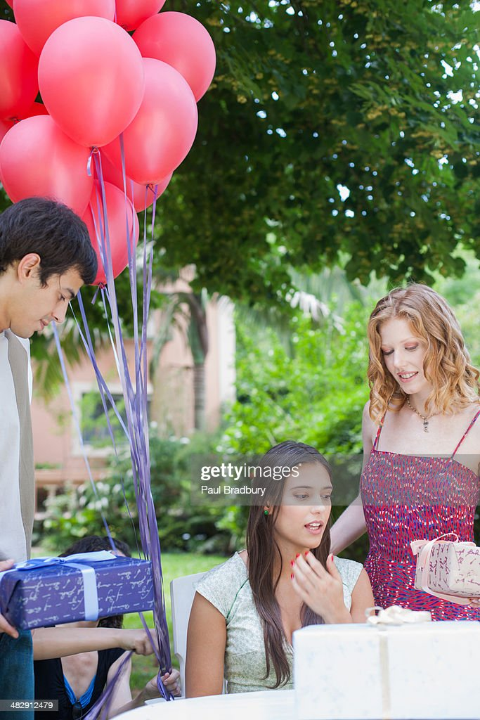 Partygoers at outdoor party giving gifts to woman  : Stock Photo