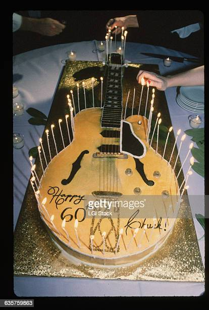 Partygoers light the candles on a cake shaped like an acoustic guitar at singer and guitarist Chuck Berry's 60th birthday party
