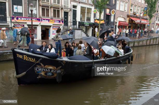 Partygoers travel on boat through red light district.