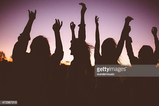 Divertimento ragazzi ballare e che si stagliano contro il cielo twilit