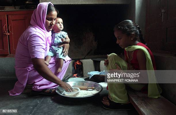STORY 'INDIAHEALTHWOMENABORTION' BY Parul Gupta Parminder Kaur makes chapatis with her daughters nine month old daughter Manpreet Kaur and seven year...