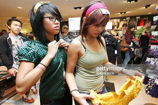 Sheryl Fernandez and her friend Amanda Zabala forgo the long line for the fitting room and try on shirts and headbands at the gran d opening of the...