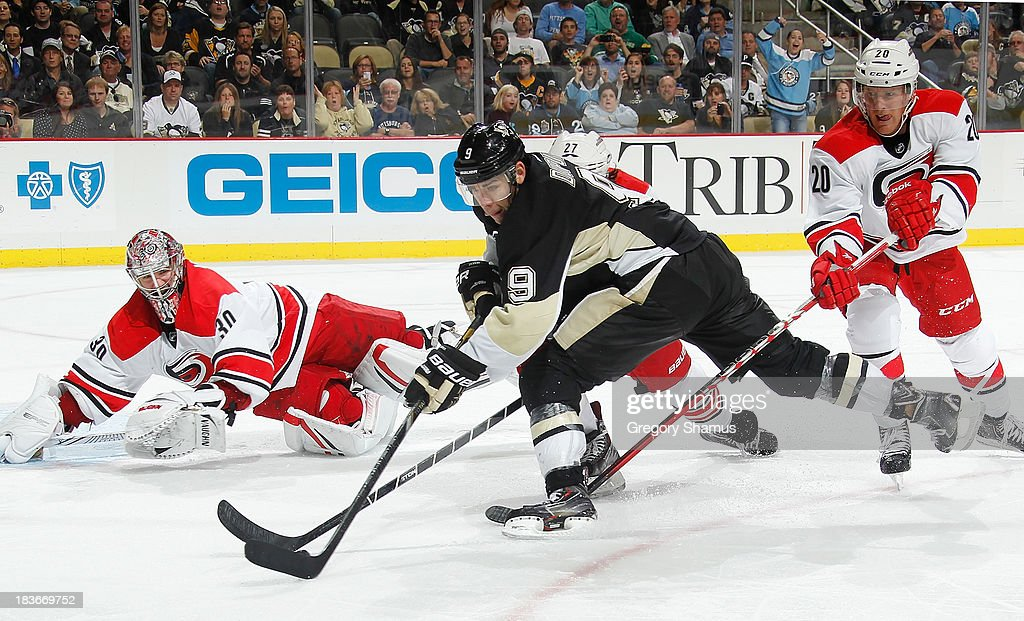 <a gi-track='captionPersonalityLinkClicked' href=/galleries/search?phrase=Pascal+Dupuis&family=editorial&specificpeople=208971 ng-click='$event.stopPropagation()'>Pascal Dupuis</a> #9 of the Pittsburgh Penguins controls the puck in front of the defense of <a gi-track='captionPersonalityLinkClicked' href=/galleries/search?phrase=Cam+Ward&family=editorial&specificpeople=453216 ng-click='$event.stopPropagation()'>Cam Ward</a> #30 and <a gi-track='captionPersonalityLinkClicked' href=/galleries/search?phrase=Riley+Nash&family=editorial&specificpeople=4324981 ng-click='$event.stopPropagation()'>Riley Nash</a> #20 of the Carolina Hurricanes on October 8, 2013 at Consol Energy Center in Pittsburgh, Pennsylvania.