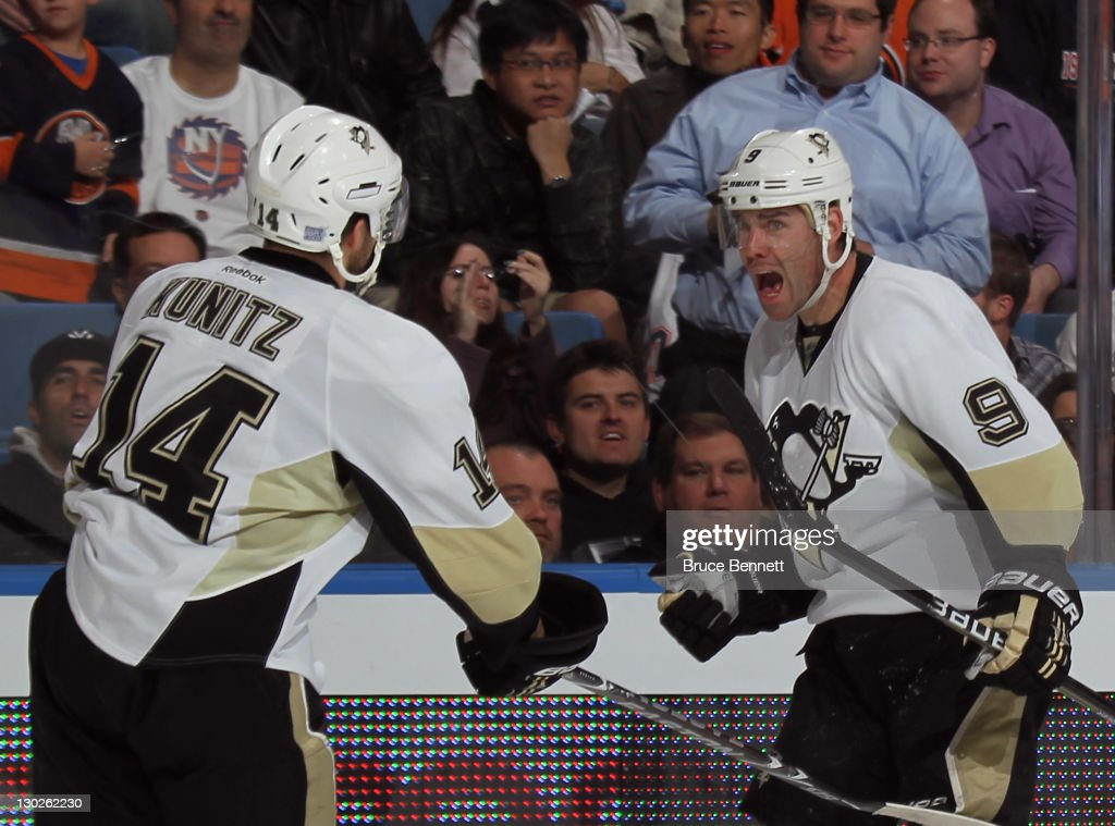 <a gi-track='captionPersonalityLinkClicked' href=/galleries/search?phrase=Pascal+Dupuis&family=editorial&specificpeople=208971 ng-click='$event.stopPropagation()'>Pascal Dupuis</a> #9 of the Pittsburgh Penguins (R) scores at 17:09 of the first period against the New York Islanders and is joined by <a gi-track='captionPersonalityLinkClicked' href=/galleries/search?phrase=Chris+Kunitz&family=editorial&specificpeople=604159 ng-click='$event.stopPropagation()'>Chris Kunitz</a> #14 (R) at Nassau Veterans Memorial Coliseum on October 25, 2011 in Uniondale, New York.