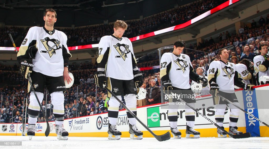 Pascal Dupuis #9, Paul Martin #7, Sidney Crosby #87 and Brooks Orpik #44 of the Pittsburgh Penguins stand on the ice during the singing of the National Anthems prior to NHL action against the Winnipeg Jets at the MTS Centre on February 15, 2013 in Winnipeg, Manitoba, Canada.