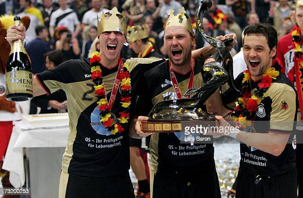 Pascal Hens Christian Schwazer and Markus Baur of Germany celebrate with the cup after winning the IHF World Championship final between Germany and...