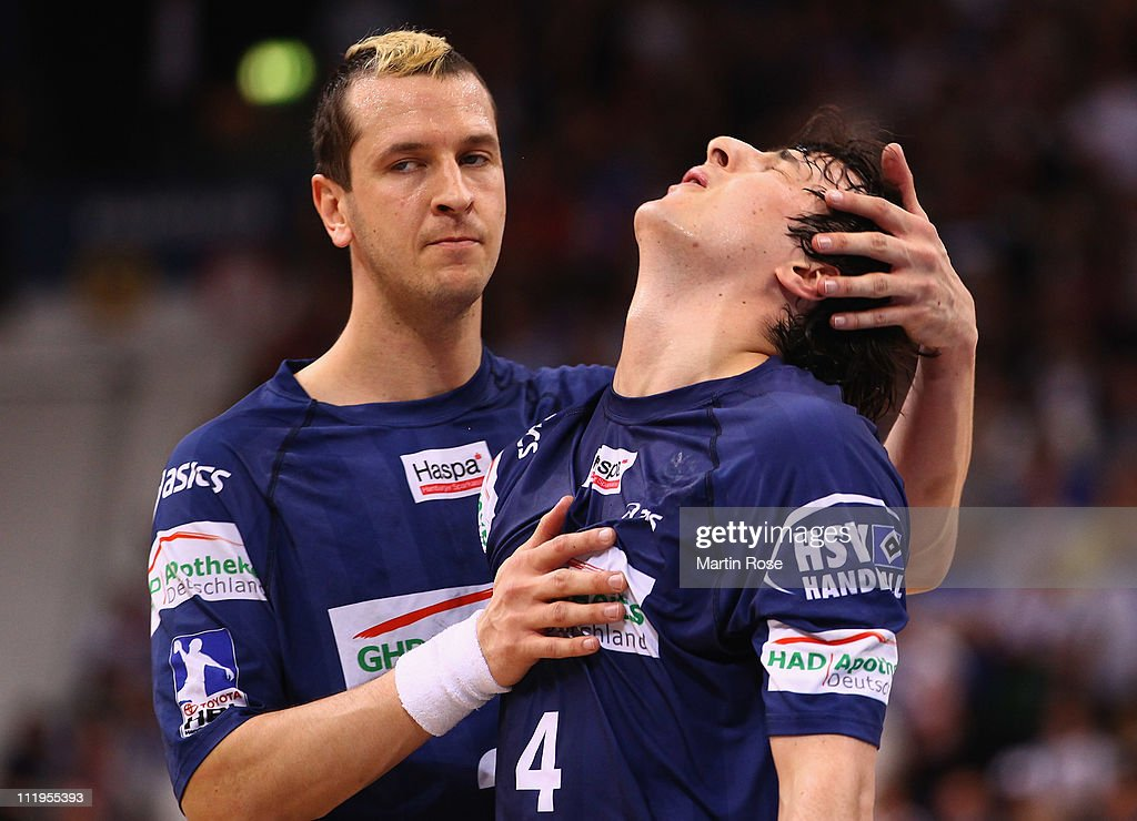 Pascal Hens (L) of Hamburg comforts team mate Domagoj Duvnjak (R) after the Toyota Handball Bundesliga match between HSV Hamburg and TV Grosswallstadt at the o2 World Arena on April 10, 2011 in Hamburg, Germany.