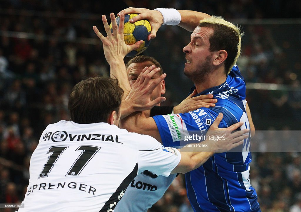Pascal Hens (R)of Hamburg is challenged by Christian Sprenger (L) and Christian Zeitz of Kiel during the Toyota Handball Bundesliga match between THW Kiel and HSV Hamburg at the Sparkassen Arena on December 11, 2011 in Flensburg, Germany.