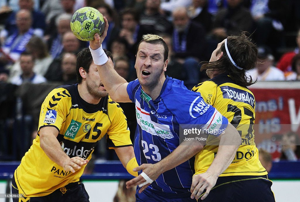 Pascal Hens of Hamburg is challenged by Ivan Cupic and Michael Mueller of RheinNeckar Loewen during the Toyota Bundesliga handball game between HSV...
