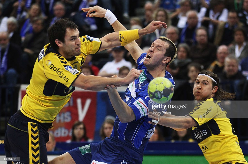 Pascal Hens (C) of Hamburg is challenged by Zarko Sesum (L) and Ivan Cupic of Rhein-Neckar Loewen during the Toyota Bundesliga handball game between HSV Hamburg and Rhein-Neckar Loewen at the O2 World on April 10, 2012 in Hamburg, Germany.