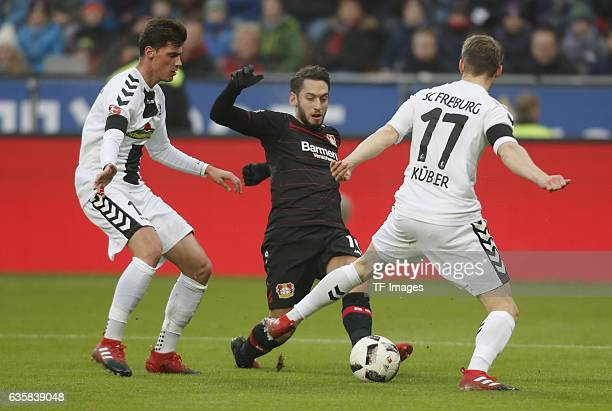 Pascal Stenzel of Freiburg and Hakan Calhanoglu of Leverkusen and Lukas Kuebler of Freiburg battle for the ball during the Bundesliga match between...