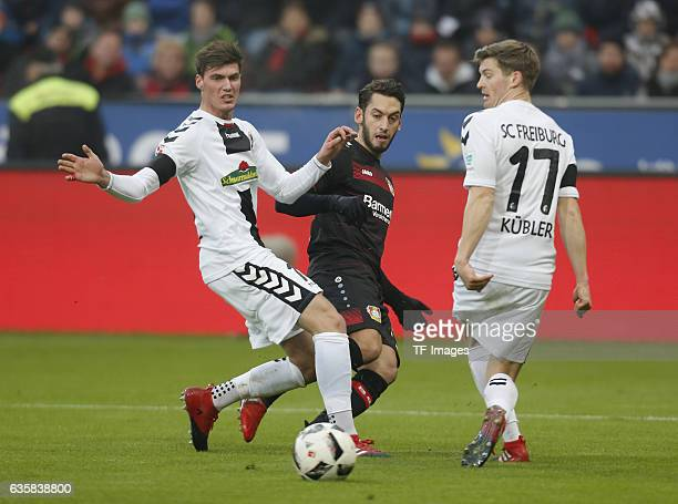 Pascal Stenzel of Freiburg and Hakan Calhanoglu of Leverkusen rechts Onur Bulut of Freiburg battle for the ball during the Bundesliga match between...