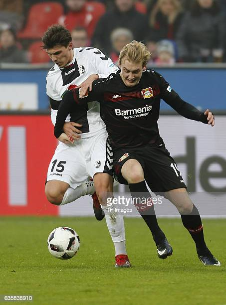 Pascal Stenzel of Freiburg and Julian Brandt of Leverkusen battle for the ball during the Bundesliga match between Bayer 04 Leverkusen and SC...