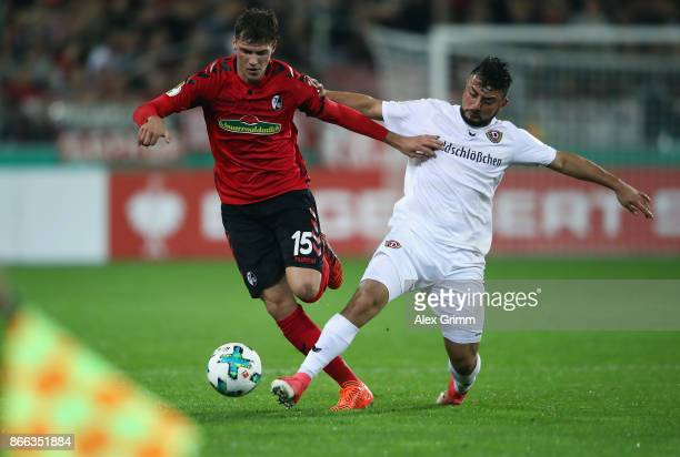 Pascal Stenzel of Freiburg is challenged by Aias Aosman of Dresden during the DFB Cup match between SC Freiburg and Dynamo Dresden at...