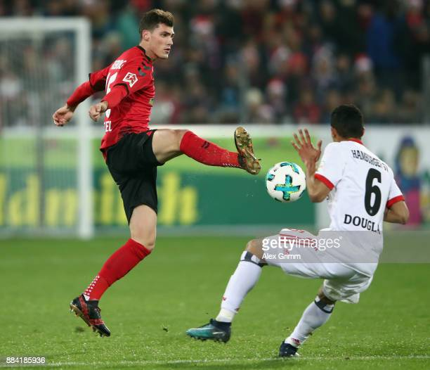 Pascal Stenzel of Freiburg is challenged by Douglas Santos of Hamburg during the Bundesliga match between SportClub Freiburg and Hamburger SV at...