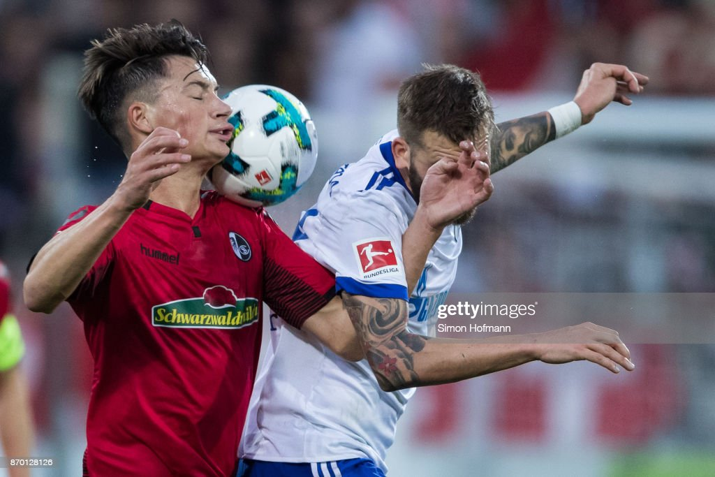Pascal Stenzel of Freiburg jumps for a header with Guido Burgstaller of Schalke during the Bundesliga match between Sport-Club Freiburg and FC Schalke 04 at Schwarzwald-Stadion on November 4, 2017 in Freiburg im Breisgau, Germany.